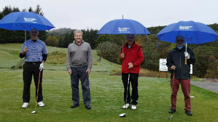 Golfers sporting their umbrellas