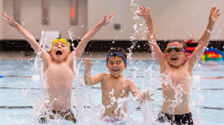 Three young boys jumping up from the water with their arms in the air