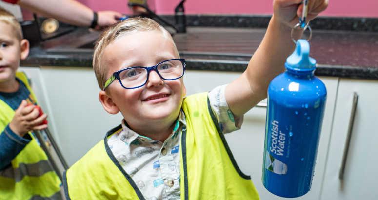 Young litter picker holding a Scottish Water refillable water bottle