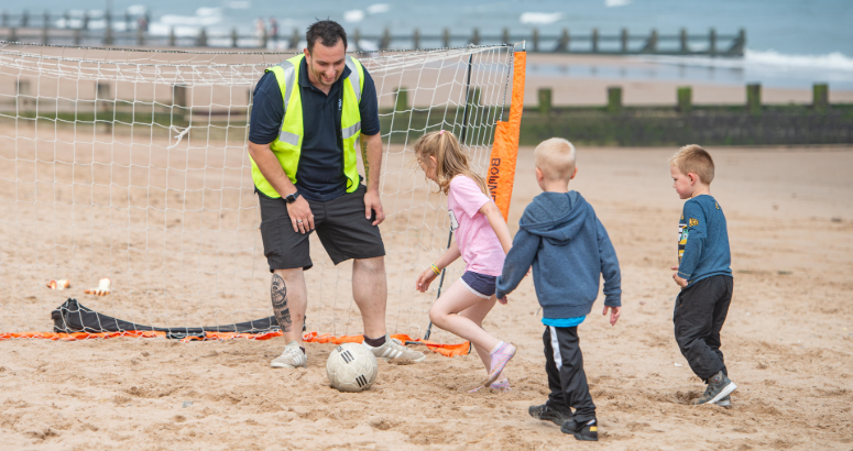 Young litter pickers having a kick about on the beach